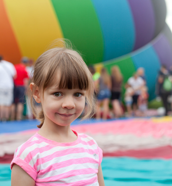 A picture of a young girl in a striped tshirt standing in front of a half-inflated rainbow-colored hot air balloon.